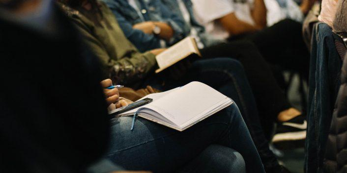 Detaljbilde av mennesker på møte med notatblokker